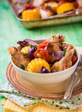 Roasted chicken with vegetables. In bowl. Chicken wings, tomato, corn and onion. Green background, selective focus, rustic Stock Image