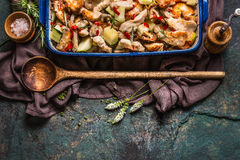 Roasted Chicken with vegetables in casserole with wooden spoon and fresh herbs on dark rustic background, top view. Border Royalty Free Stock Images