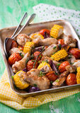 Roasted chicken with vegetables. In metal baking tray. Chicken wings, tomato, corn and onion. Green background, selective focus Royalty Free Stock Images
