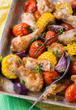 Roasted chicken with vegetables. In metal baking tray. Chicken wings, tomato, corn and onion. Green background, selective focus Stock Images