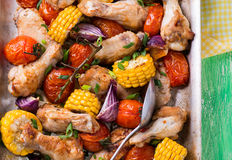 Roasted chicken with vegetables. In metal baking tray. Chicken wings, tomato, corn and onion. Green background, selective focus, closeup, top view Royalty Free Stock Photography
