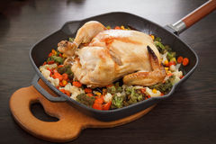 Roasted chicken and vegetables. In pan on the wooden table Stock Images