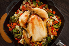Roasted chicken and vegetables. In pan on the wooden table Stock Photography