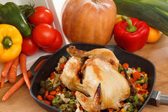 Roasted chicken and vegetables. In pan on the wooden table Stock Photos