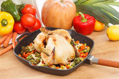 Roasted chicken and vegetables. In pan on the wooden table Stock Image