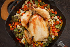 Roasted chicken and vegetables. In pan on the wooden table Royalty Free Stock Photo