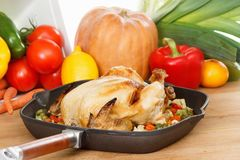 Roasted chicken and vegetables. In pan on the wooden table Royalty Free Stock Photos