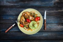 Roasted chicken with vegetables and green mashed potatoes. Fork, knife on a colored wooden background. Top view. Roasted chicken with vegetables tomatoes Stock Photography