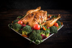 Roasted chicken with vegetables. On wooden background Stock Image