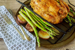 Roasted chicken and vegetables on the wooden table with. Grill chicken asparagus baked potatoes Royalty Free Stock Photography