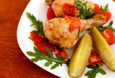 Roasted chicken on white plate on wooden table. Simple food Stock Photos