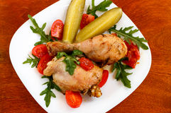 Roasted chicken on white plate on wooden table Stock Images