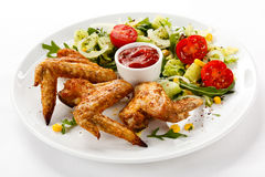 Roasted chicken wings. And vegetables stock images