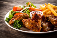 Roasted chicken wings. French fries and vegetables Royalty Free Stock Photo