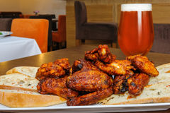 Roasted chicken wings and glass of beer Stock Photo
