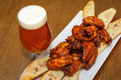 Roasted chicken wings and glass of beer Royalty Free Stock Image