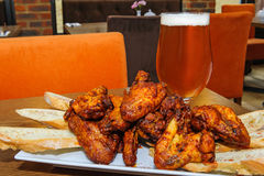 Roasted chicken wings and glass of beer stock image