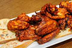 Roasted chicken wings. Hot roasted chicken wings on a plate with slices of  baguette Stock Image