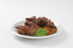 Roasted chicken wings. Plate of roasted chicken wings on white background stock image