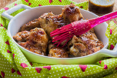 Roasted chicken wings in white baking dish. Cooked with sauce from mustard, honey and soy sauce Royalty Free Stock Photo