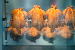 Roasted chickens on rotisserie at market