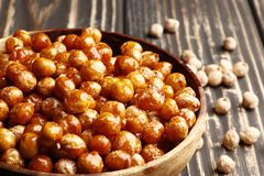 Roasted chickpeas in a bowl on a wooden background stock photos