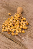 Roasted chickpeas. In a scoop on a wooden background Stock Photos