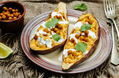Roasted chickpeas stuffed sweet potato with Greek yogurt cilantro lime dressing. Toning. selective focus stock images