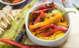Roasted chili Peppers for making of a curry or chili sauce. Roasted Red orange and green chili Peppers in pestle with mortar and Grilled red  green and orange Stock Photos