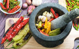 Roasted chili Peppers in pestle with mortar. Roasted Red orange and green chili Peppers in pestle with mortar and Grilled red  green and orange chili Peppers on Royalty Free Stock Images