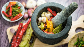 Roasted chili Peppers in pestle with mortar. Roasted Red orange and green chili Peppers in pestle with mortar and Grilled red  green and orange chili Peppers on Stock Photos