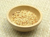 Roasted chopped hazelnuts. Wooden bowl with roasted chopped hazelnuts on rattan underlay Royalty Free Stock Image
