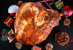 Roasted Christmas ham on board with festive decoration. top view, background Royalty Free Stock Photo