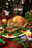 Roasted Christmas Turkey. Christmas-decorated table with feast, gifts, roasted turkey, candles, champagne, and Christmas tree on back Stock Images
