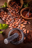 Roasted cocoa beans. Being ground in mortar and pestle Royalty Free Stock Photos