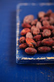 Roasted cocoa chocolate beans on dark blue wood stock images