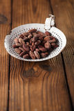 Roasted cocoa chocolate beans in old enamel sieve, textured  woo Stock Photography