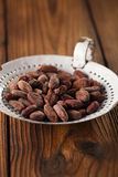 Roasted cocoa chocolate beans in old enamel sieve, textured  woo Royalty Free Stock Photography