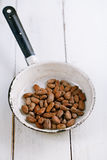 Roasted cocoa chocolate beans in pan on white wood table Royalty Free Stock Images