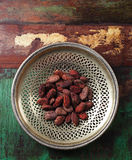 Roasted cocoa chocolate beans in silver dish on  wood background Royalty Free Stock Images