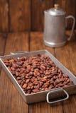 Roasted cocoa chocolate beans in Vintage heavy cast aluminum roa Stock Photos