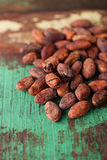 Roasted cocoa chocolate beans on wood background Royalty Free Stock Image