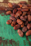 Roasted cocoa chocolate beans on wood background Stock Photography