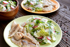 Roasted cod with fresh radish, lettuce and arugula salad. A plate of healthy roasted cod with fresh radish, lettuce and arugula salad on a wooden background Stock Photos