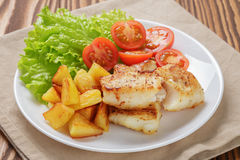 Roasted codfish fillet with vegetables. Selective focus Stock Photos