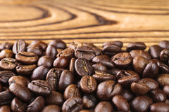 Roasted coffee bean arabica on wooden table, close-up, selective focus. Macro shots Stock Images