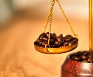 Roasted coffee bean on weight scale on wooden table royalty free stock image