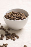 Roasted coffee beans. In a white bowl on jute sacking Royalty Free Stock Image