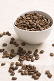 Roasted coffee beans. In a white bowl on jute sacking Royalty Free Stock Images