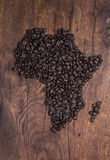 Roasted coffee beans arranged in the shape of Africa on old wood Royalty Free Stock Photos